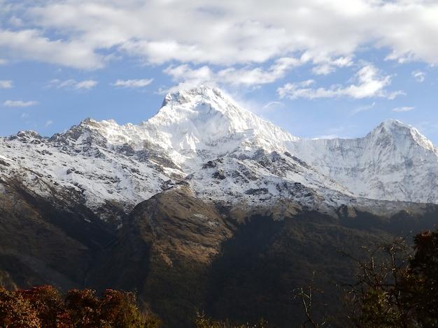 Spitze des schneebedeckten felsenberges auf bewölktem hintergrund Premium Fotos