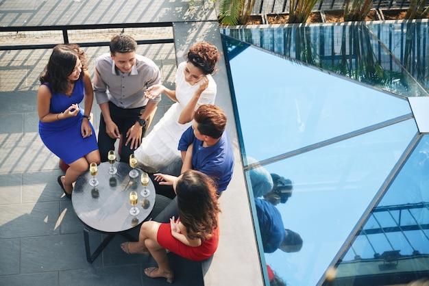 Spitzenschuß der gruppe parteigäste, die um tabelle mit getränken terrasse an der im freien sitzen Kostenlose Fotos