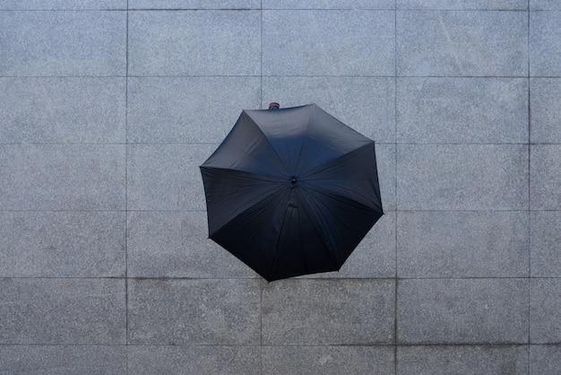 Spitzenschuß der unerkennbaren person stehend unter regenschirm auf pflasterung Kostenlose Fotos