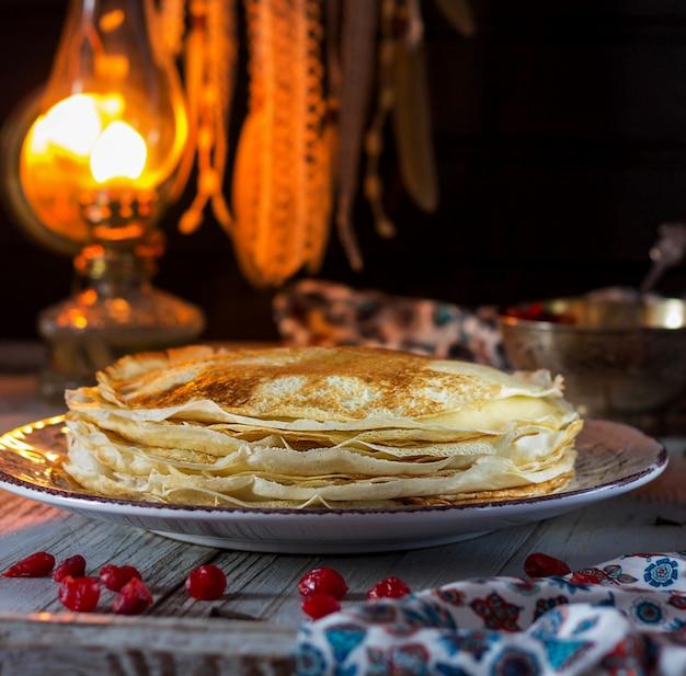 Spitzepfannkuchen und -kirsche auf dem tisch. pfannkuchenwoche Premium Fotos