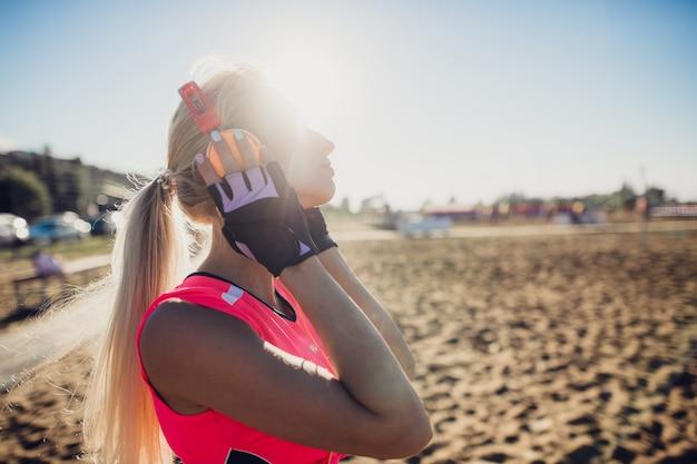 Sport-außenfoto der schönen jungen blonden frau im rosa bunten sportanzug, der musik auf kopfhörern am strand hört Premium Fotos