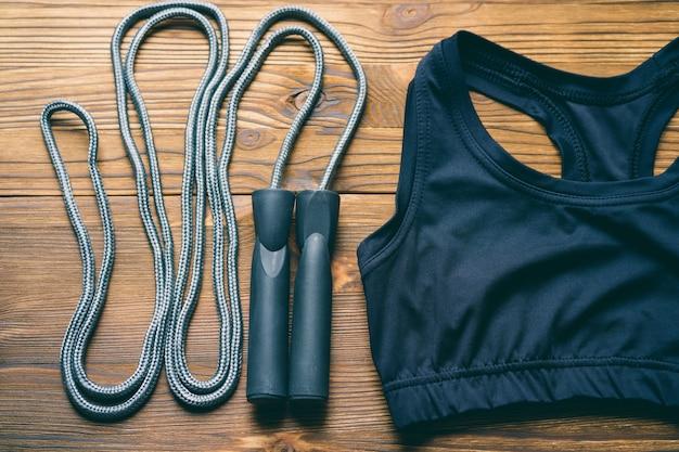 Sport-bh und springseil auf hölzernem hintergrund Premium Fotos