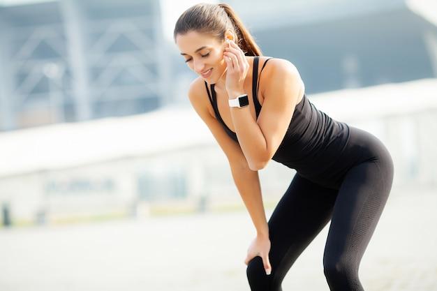 Sport im freien. hörende musik der frau am telefon beim draußen trainieren Premium Fotos