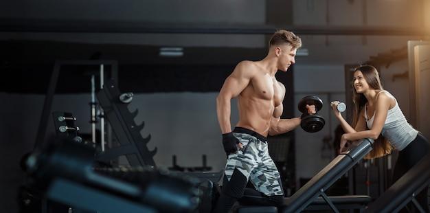 Sport, training, eignung, lebensstil und leutekonzept - junge frau mit dem persönlichen trainer, der zurück und bauchmuskeln auf bank in der turnhalle biegt Premium Fotos