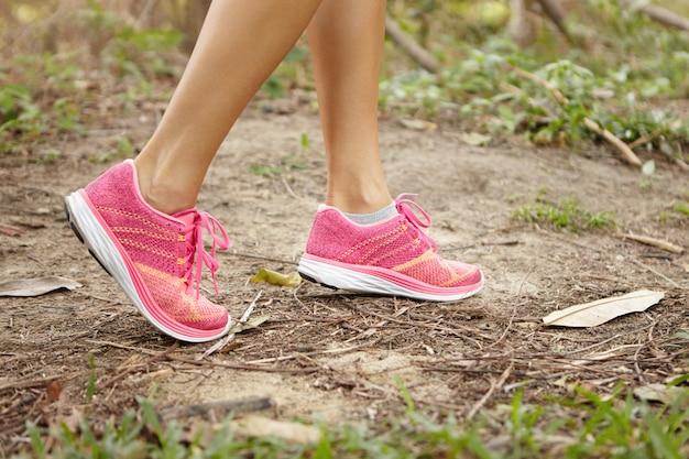 Sport- und abenteuerkonzept. schließen sie herauf schuss von weiblichen beinen, die rosa laufschuhe im wald tragen, während in der sommernatur trainieren. Kostenlose Fotos