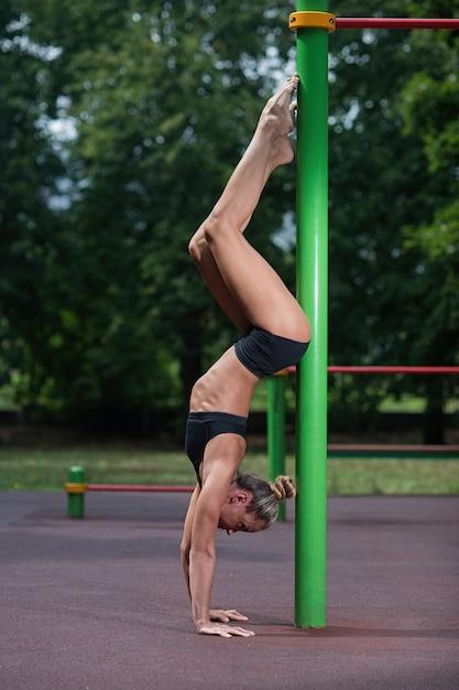 Sportakrobatikmädchen steht auf ihren händen und macht ein akrobatisches element Premium Fotos