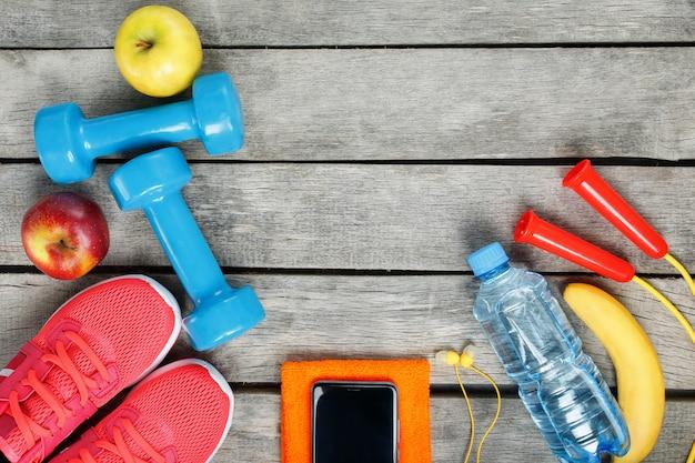 Sportausrüstung und der smartphone mit kopfhörern auf einem hölzernen Premium Fotos