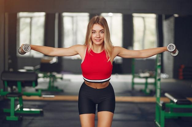 Sportblondine in einem sportbekleidungstraining in einem fitnessstudio Kostenlose Fotos