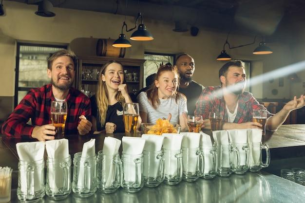 Sportfans jubeln in der bar, im pub und trinken bier, während die meisterschaft und der wettbewerb stattfinden Kostenlose Fotos