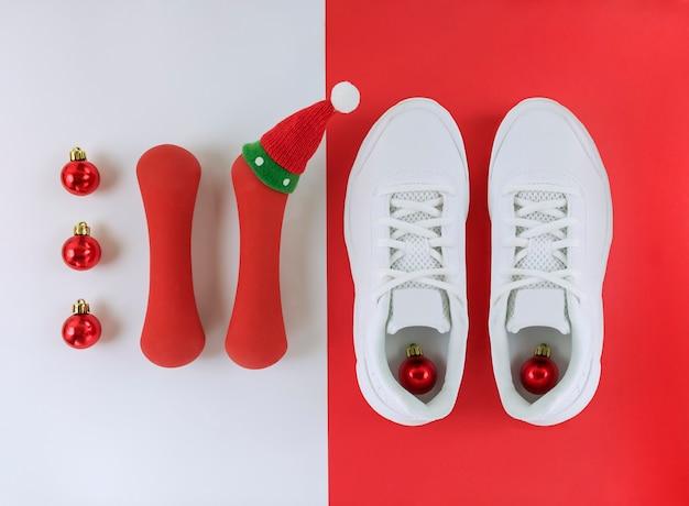 Sportferienwohnung lag. weihnachtskugeln, turnschuhe und hanteln mit süßem hut auf weißem und rotem boden. Premium Fotos
