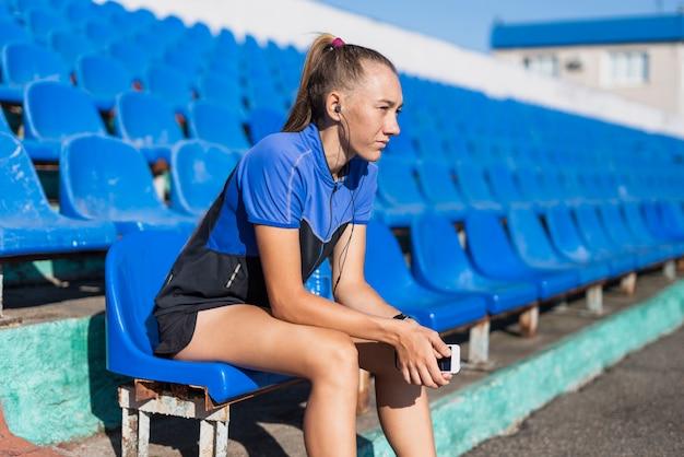 Sportive frau am stadionsitzen Kostenlose Fotos