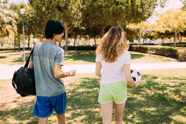 Sportive jugendfreunde, die entlang park gehen Kostenlose Fotos