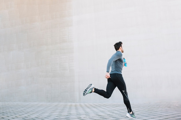 Sportiver athlet, der auf straße läuft Kostenlose Fotos