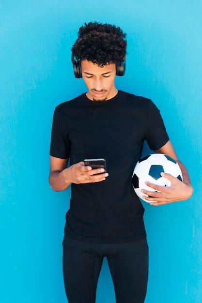 Sportiver junger mann, der telefon hält und verwendet Kostenlose Fotos