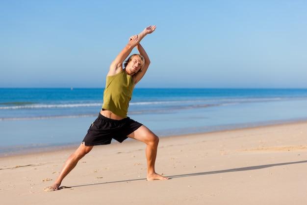 Sportiver mann macht gymnastik am strand Premium Fotos