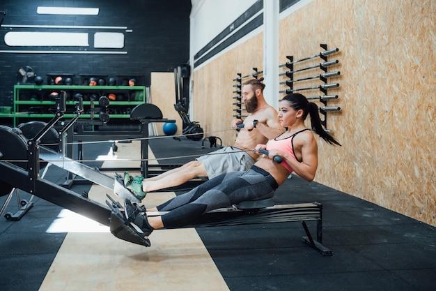 Sportives paar cross fit training rudern auf rudergerät Premium Fotos