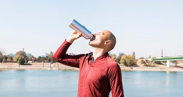 Sportives trinkwasser des jungen mannes von der flasche, die nahe dem see steht Kostenlose Fotos