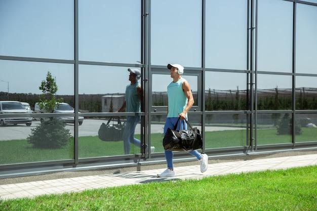 Sportler gegen modernes glasgebäude, flughafen in megapolis Kostenlose Fotos