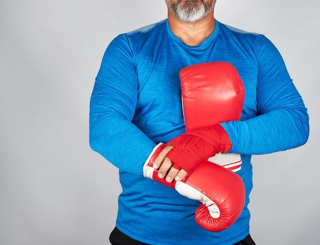 Sportler in blauer kleidung, hände mit rotem textilverband umwickelt Premium Fotos