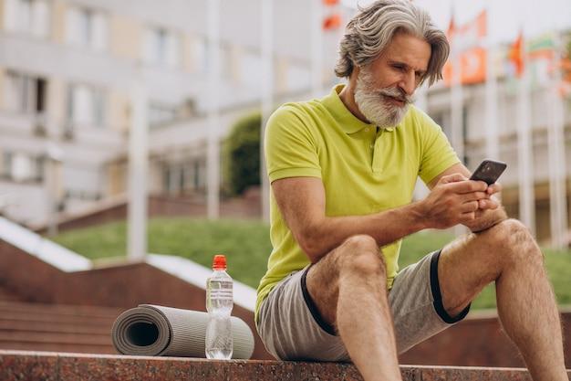 Sportler mittleren alters sitzen auf treppen mit telefon Kostenlose Fotos