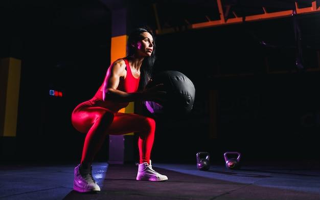 Sportlerin, die hockenübungen mit eignungsball tut. frau, die mit medizinball an der turnhalle trainiert und ausdehnt Premium Fotos