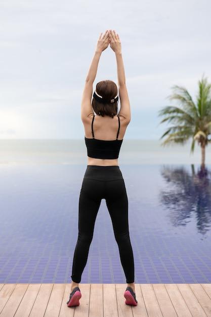 Sportlerin, die sich ausdehnt und sich darauf vorbereitet, am morgen am pool zu rennen. Premium Fotos