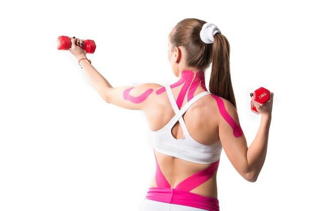 Sportlerin hält hanteln mit aufklebern auf schultern und nacken Premium Fotos