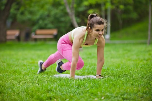Sportlich fit frau, die aerobic-übung auf einer matte im park im freien macht Premium Fotos