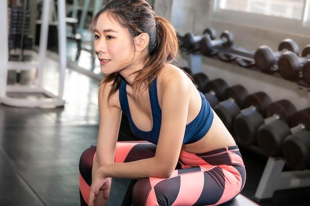 Sportlich schöne frau fit und gesund lächelnd in der turnhalle nach dem training. Premium Fotos