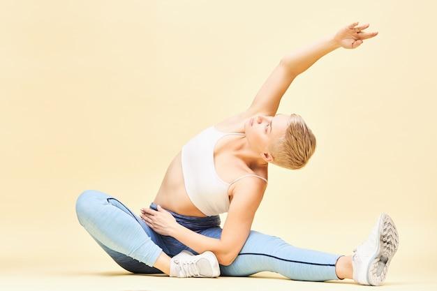 Sportliche flexible junge frau in stilvoller sportbekleidung, die yoga in sitzender position macht, sich seitlich beugt, die rippen erweitert und eine hand nach oben streckt. knabenhaftes mädchen, das pilates übt, auf boden sitzt, sich streckt Kostenlose Fotos