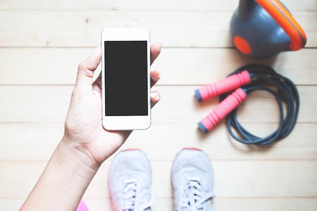 Sportliche frau der draufsicht, die intelligentes telefon hält. mockup für mobile anwendungen. Premium Fotos