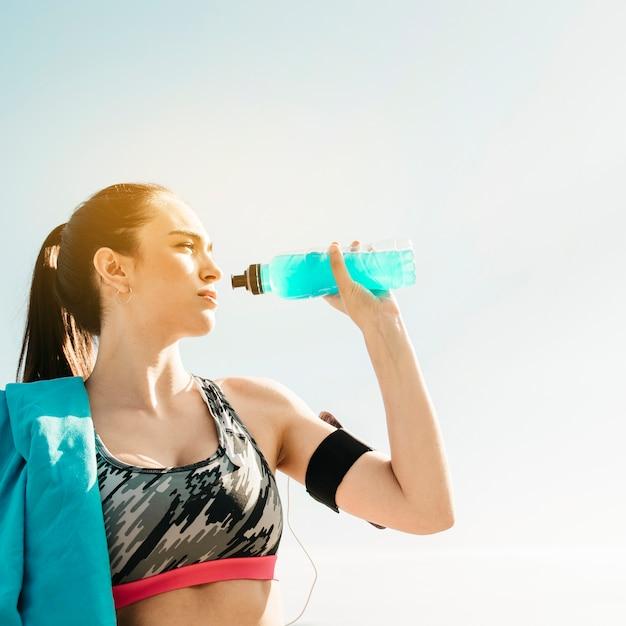 Sportliche frau, die auf himmelhintergrund trinkt Kostenlose Fotos