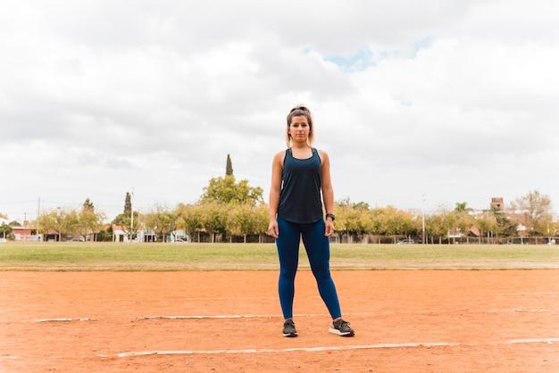 Sportliche frau, die auf stadionsbahn steht Kostenlose Fotos