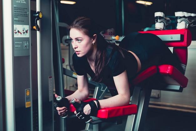 Sportliche frau, die eignungsübung in der turnhalle tut Kostenlose Fotos