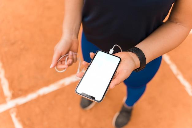 Sportliche frau, die smartphoneschablone darstellt Kostenlose Fotos
