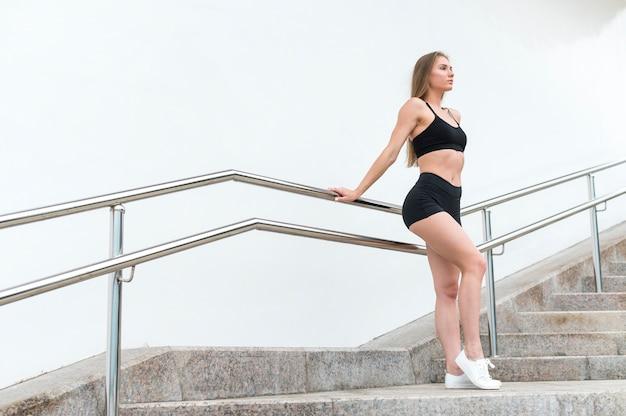 Sportliche frau, die weg stillsteht und schaut Kostenlose Fotos
