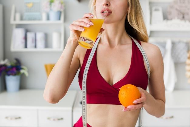 Sportliche frau in der küche mit gesundem saft Kostenlose Fotos