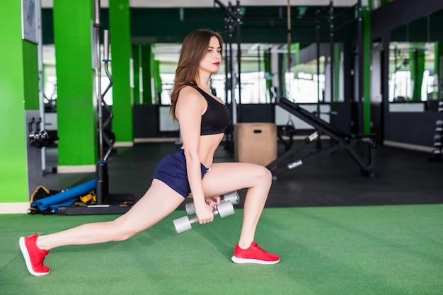 Sportliche frau mit starkem körper macht verschiedene übungen im modernen sportclub mit spiegeln Kostenlose Fotos