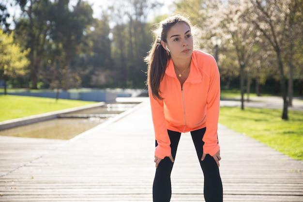 Sportliche hübsche dame, die auf knien sich lehnt und im stadtpark sich entspannt Kostenlose Fotos