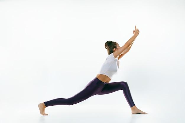Sportliche junge frau, die yoga-praxis isoliert tut. fit flexibles weibliches modell üben. konzept eines gesunden lebensstils und eines natürlichen gleichgewichts zwischen körperlicher und geistiger entwicklung. Kostenlose Fotos