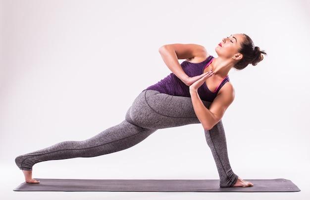 Sportliche junge frau, die yoga-praxis lokalisiert auf weißem hintergrund tut - konzept des gesunden lebens und des natürlichen gleichgewichts zwischen körper und geistiger entwicklung Kostenlose Fotos