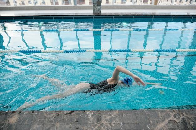 Sportliche junge frau im mützenschwimmhub allein im modernen pool mit sauberem wasser Premium Fotos