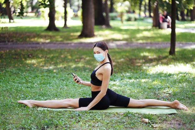 Sportliche junge frau in einer medizinischen schutzmaske, die yoga im park macht Kostenlose Fotos