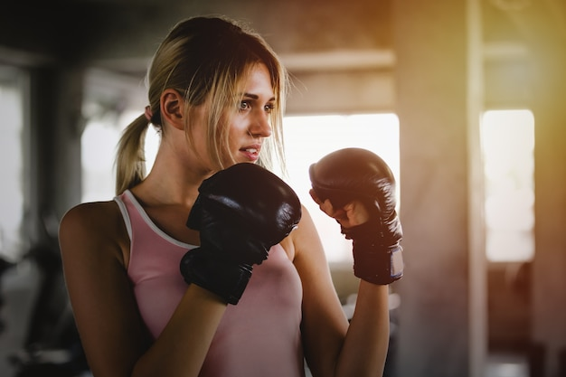 Sportliche mädchenschönheit des porträts mit den hinteren boxhandschuhen ausbildend an der turnhalle Premium Fotos