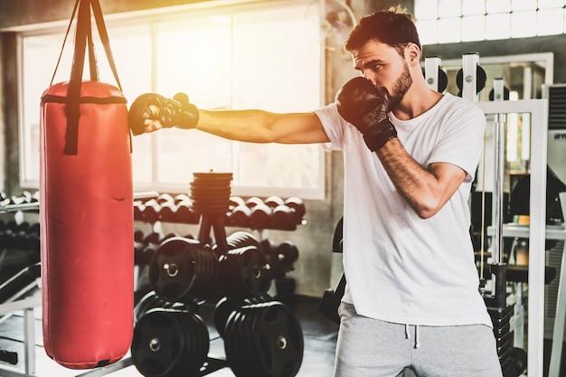 Sportliche männer des porträts mit den hinteren boxhandschuhen, die an der turnhalle ausbilden Premium Fotos