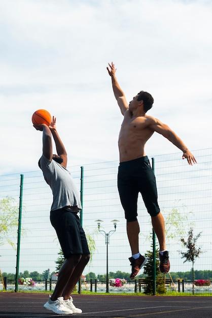 Sportliche männer, die auf basketballplatz springen Kostenlose Fotos