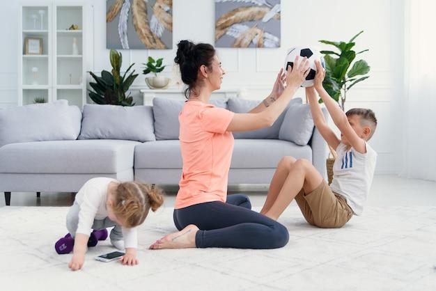 Sportliche mutter mit sohn beim morgendlichen training zu hause. mutter und sohn machen übungen zusammen, gesundes familienlebensstilkonzept Premium Fotos