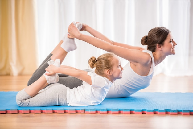 Sportliche mutter und tochter, die yogaübungen tut. Premium Fotos