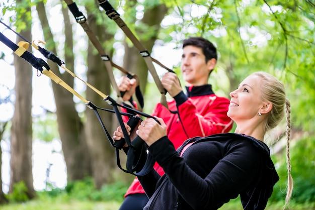 Sportliche paare am schlingentrainer, der eignung tut Premium Fotos