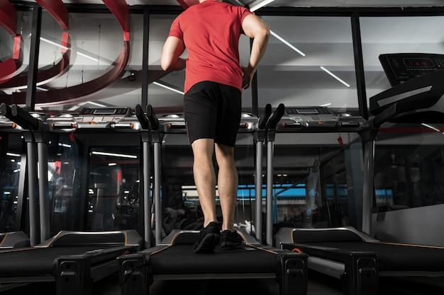 Sportlicher junger mann, der im fitnessstudio läuft Premium Fotos